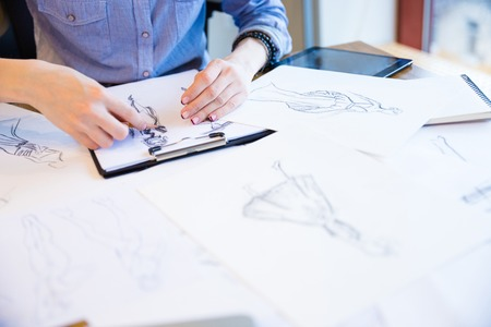 creating: Closeup of hands of young woman fashion designer creating new collection of clothes and drawing sketches on clipboard Stock Photo