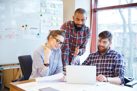 Grupo multiétnico de hombres de negocios feliz trabajando con el ordenador portátil en la oficina