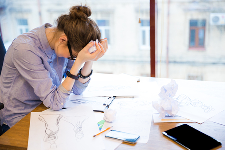 despaired: Sad despaired young woman fashion designer sitting in office with sketches on table