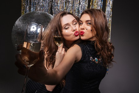 ball isolated: Two happy playful young women sending kisses and drinking champagne near disco ball over black background