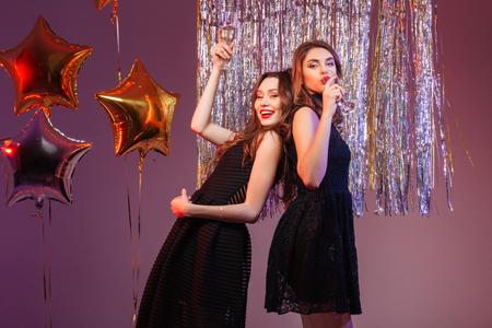보라색 배경 위에 샴페인을 마시고 검은 드레스에 행복한 두 여자 스톡 콘텐츠