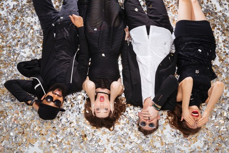 Top view of multiethnic group of funny young friends grimacing and lying on sparkling confetti background Stock Photo