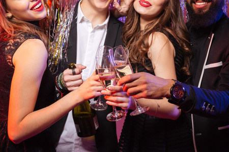 Closeup of bottle and glasses of champagne holded by group of happy young friends