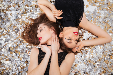 seductive women: Top view of two seductive beautiful young women with red lips  lying on background of shining confetti