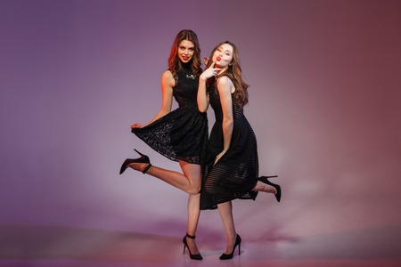 Full length portrait of a charming two women in night black dress posing over purple background Stock Photo