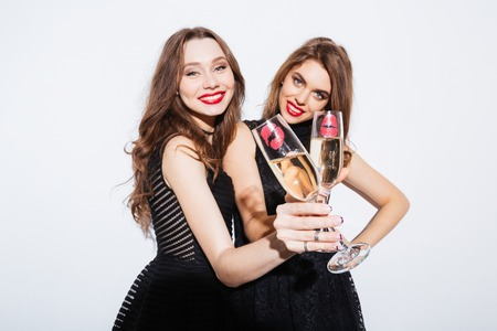 Smiling two women in night dress holding glass with champagne isolated on a white background Stockfoto