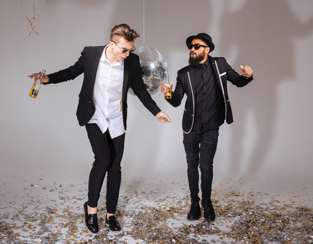 contemporary dance: Full length of two handsome male friends in black suits and sunglasses dancing and drinking beer over white background