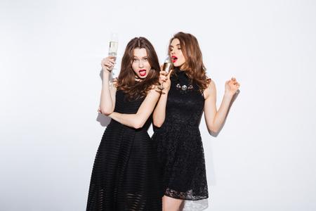 아 하이트 배경에 고립 된 밤 드레스 샴페인을 마시는 두 매력적인 여성 스톡 콘텐츠