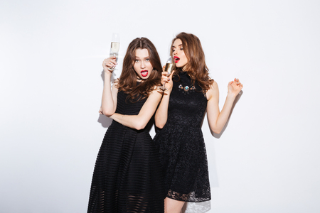 Two attractive women in night dress drinking champagne isolated on aw hite background