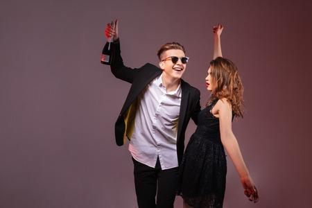feliz pareja de jóvenes con una botella de champán y bailando sobre fondo morado
