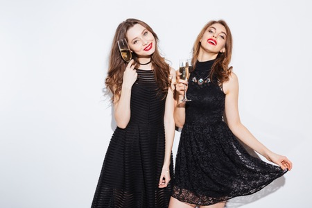 blak and white: Happy two women in blak dress holding glass with champagne isolated on a white background