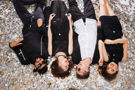 elegant party: Group of joyful beautiful young people relaxing and lying on background of shining confetti