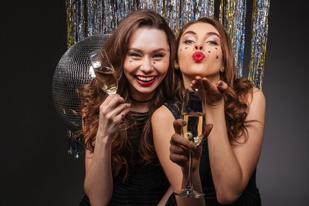 Cheerful beautiful young women having party and sending kiss over black background Standard-Bild