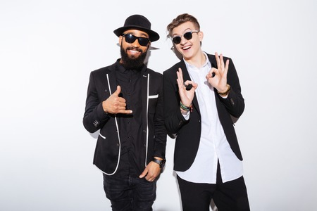 two persons: Two cheerful attractive young men standing and showing ok gesture over white background