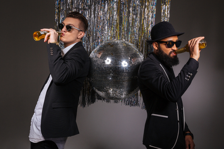 near beer: Two handsome confident young men in black suits and sunglasses standing near disco ball and drinking beer over black background Stock Photo