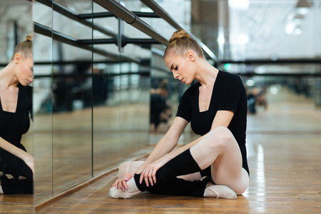 a rehearsal: Injured ballerina in pointes sitting on the floor in ballet class