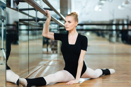 suppleness: Beautiful ballerina doing stretching exercises in ballet class Stock Photo