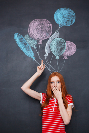 redhead woman: Amazed redhead young woman standing over blackboard background with drawn balloons Stock Photo