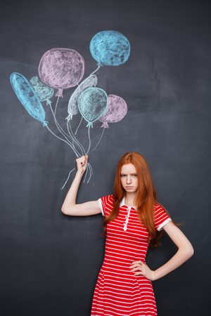 redhead girl: Sad redhead girl standing and holding drawn colorful balloons over blackboard background Stock Photo