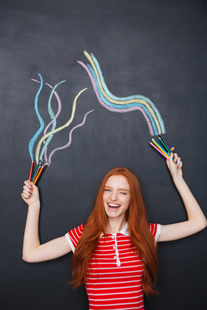 long red hair: Charming cheerful young woman with long red hair laughing and drawing on blackboard background