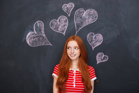 mujer enamorada: Beautiful tender young woman with long red hair standing over chalkboard with drawn hearts behind her