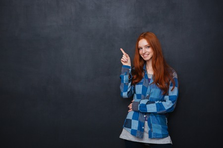20 29 years: Smiling attractive redhead young woman in checkered shirt pointing on copyspace over chalkboard background