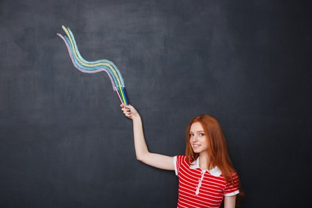 redhead woman: Smiling pretty redhead young woman drawing wave with colorful pencils on blackboard background