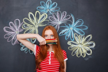 redhead woman: Wondered redhead young woman covered face with colorful pencils standing over chalkboard with drawn flowers Stock Photo