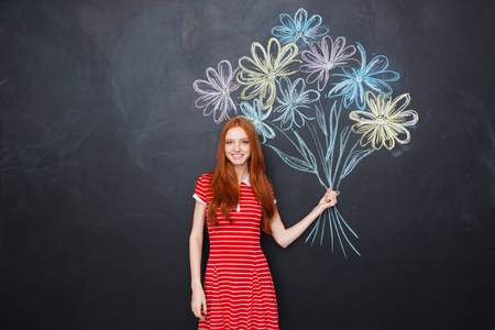 Smiling attractive redhead young woman standing and holding bouquet of drawn flowers over blackboard background