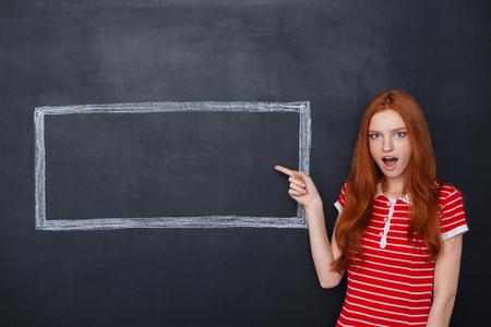 프레임 내부에 copyspace 가리키는 놀라 울 귀여운 빨간 머리 여자는 칠판 배경에 그려진