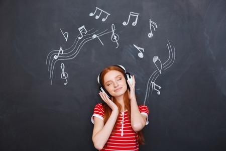 ojos negros: Relajada sonrisa hermosa mujer joven escuchando música en los auriculares sobre el fondo de la pizarra Foto de archivo