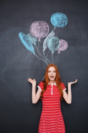 long red hair: Surprised excited young woman with long red hair standing over chalkboard background with drawn balloons