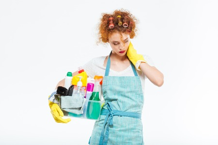 service occupation: Exhausted redhead young woman in curlers and yellow gloves holding plastic box with cleaning supplies and having neck pain over white background