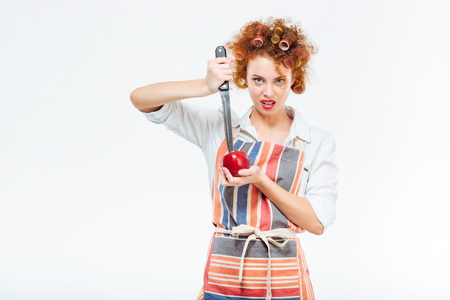 ama de casa: manzana de corte del ama de casa con el cuchillo grande aislado en un fondo blanco
