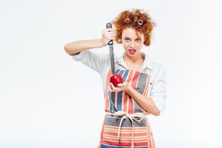 casalinga: mela taglio casalinga con grande coltello isolato su uno sfondo bianco Archivio Fotografico