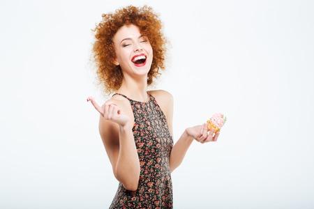 Lachen Rothaarige Frau isst Kuchen auf einem weißen Hintergrund Standard-Bild