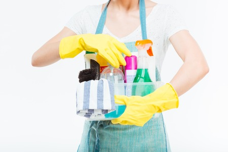 plactic: Closeup of cleaning supplies in plactic box holded by young housewife in blue kitchen apron over white background