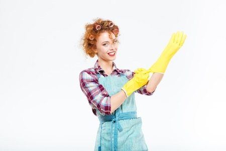 housewife gloves: Happy beautiful young housewife in blue apron wearing yellow gloves over white background