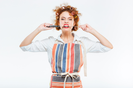 young knife: Beautiful curly young housewife in kitchen apron holding and biting big knife over white background