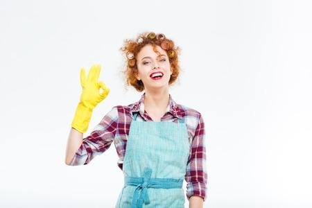 servicio domestico: ama de casa joven rizada feliz en delantal azul y guantes de color amarillo que muestra la autorizaci�n del gesto sobre el fondo blanco