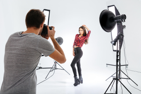 Photographer working with model in equipped studio