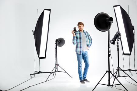 Ritratto integrale di un giovane fotografo che sta con la macchina fotografica della foto in studio