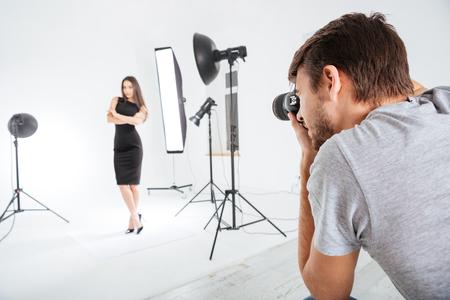 Fotografo di lavoro con il modello in studio con softbox