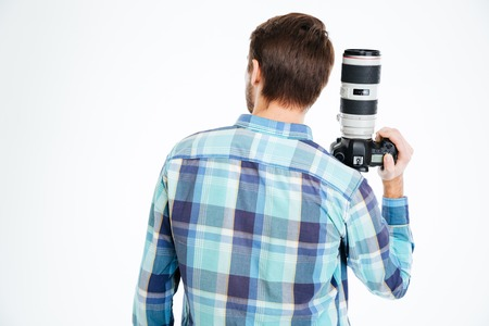 holding back: Back view portrait of a male photographer holding photo camera isolated on a white background Stock Photo