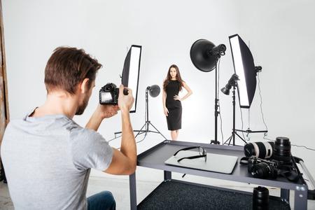 hombre disparando: Hombre disparando modelo femenino en el estudio con equipos