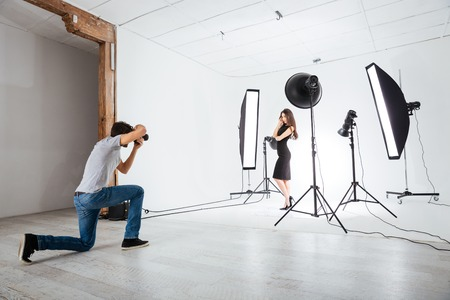 portrait young girl studio: Photographer working with model in studio with equipments