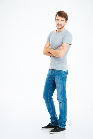 白い背景上に分離されて腕を組んで立っているカジュアルな布の handome 男の完全な長さの肖像画
