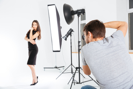Man shooting female model in studio with softboxes Stock Photo