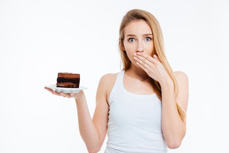 confused face: Beautiful confused young woman on diet holding piece of chocolate cake over white background