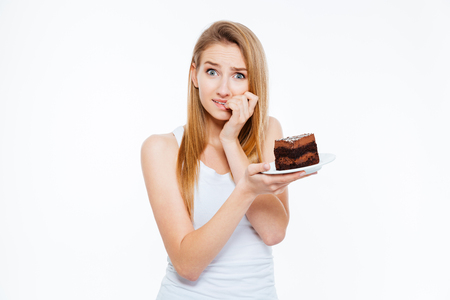 indefinitely: Doubtful pretty young woman on diet thinking and holding piece of cake over white background